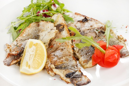 Grilled fish fillet with tomato and lemon photo