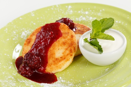 Cheese pancakes with sour cream and jam photo