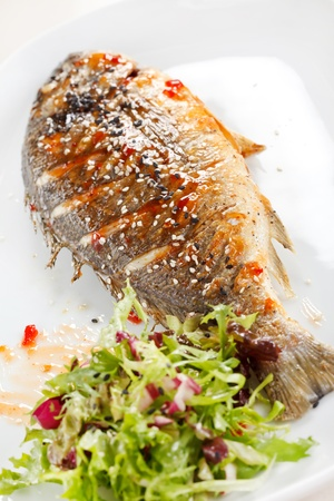 side salad: fried fish with fresh herbs and lemon  Stock Photo