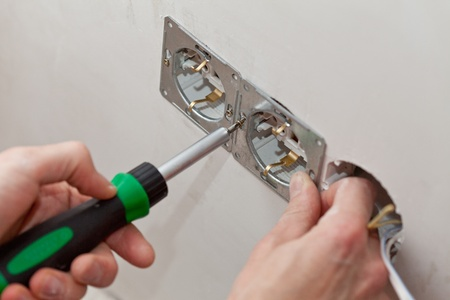 toma corriente: Las manos de un electricista Foto de archivo
