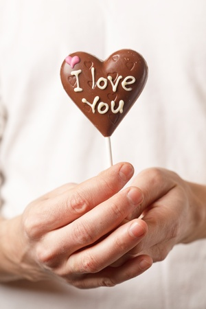 man with chocolate heart in the hands photo