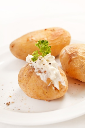 Baked potato filled with soft cheese photo