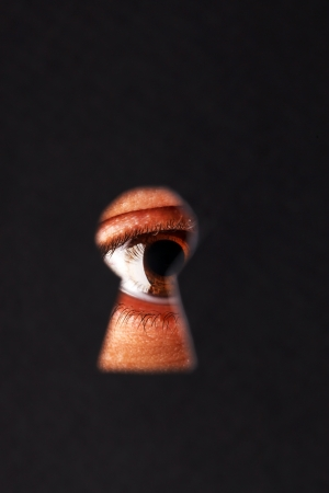 eye hole: Eye looking through a keyhole