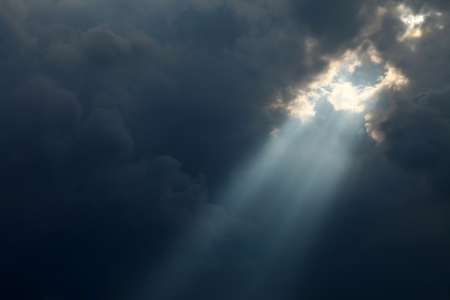 stormy sky with a dramatic sunbeam photo
