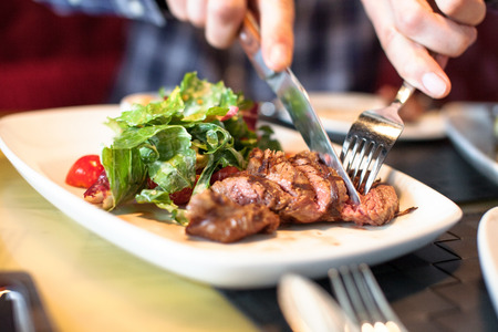 man eating: man eating meat with salad Stock Photo