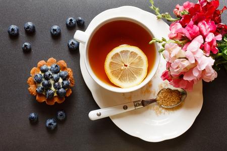 comida inglesa: taza de té con torta y flores