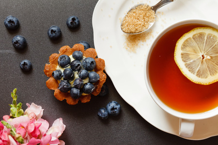 english breakfast tea: cup of tea with cake and flowers