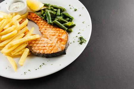 grilled salmon steakk with french fries photo