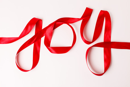 Joy word written in red ribbon on white background Stock Photo