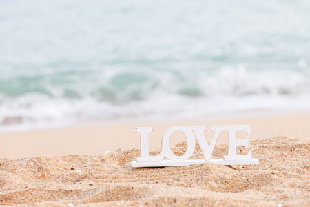 wedding beach: wooden letters spelling the word love on a tropical beach