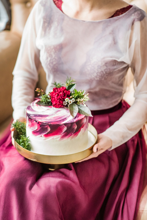 cakestand: Woman holding a wedding cake Stock Photo