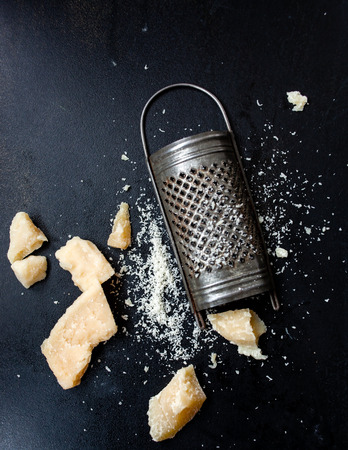 cheese grater: Parmesan cheese with a grater