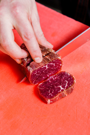 cutting meat: chef cutting meat Stock Photo