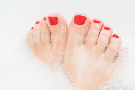 Feet with red nails soaking in spa bath