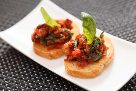 Bruschettas con tomate picado y la albahaca Foto de archivo - 67901150