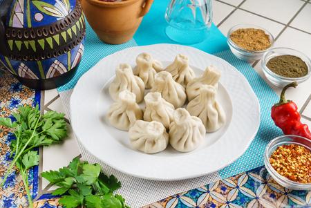 Georgian dumplings Khinkali with meat, greens and tomato spicy sauce Satsebeli on white plate