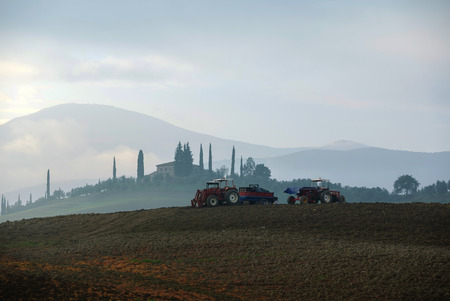 토양 경운기로 땅을 준비하는 트랙터의 농부