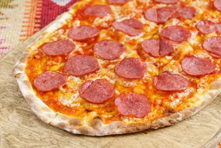 나무 보드에 살라미 소시지와 함께 피자
