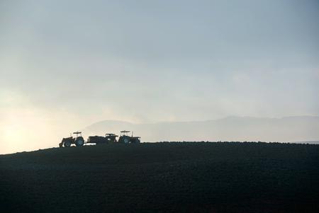 苗床の耕運機と土地を準備するトラクターの農家 写真素材