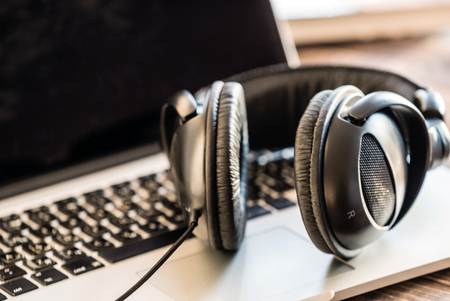 koptelefoon op de laptop Stockfoto
