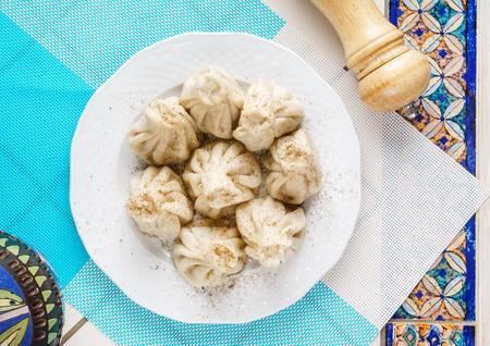 그루지야 문자 만 두, 고기, 채소, 토마토 매운 소스와 함께 Khinkali 접시에 Satsebeli