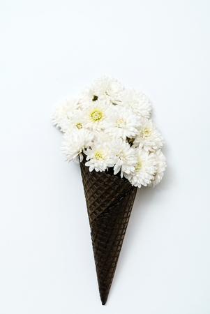 white chrysanthemum flowers in black waffle cone