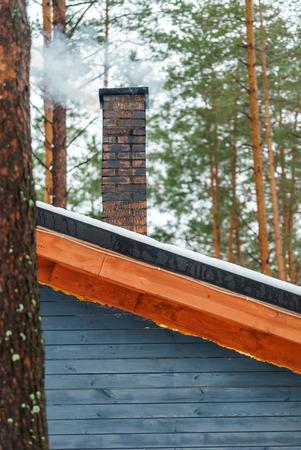 冬の日に家の煙突から白い煙が出る 写真素材