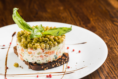russian salad on wooden background