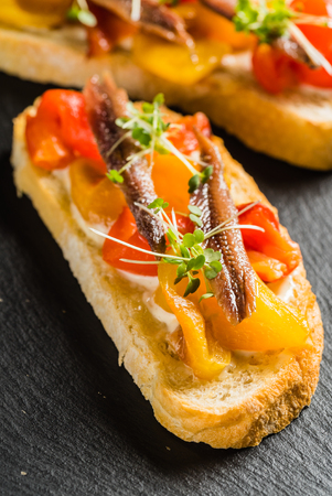 tomato and anchovy crostini on cutting board