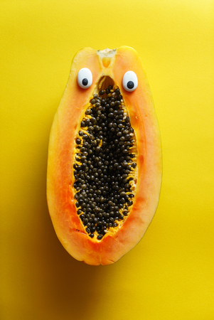 funny papaya on yellow background