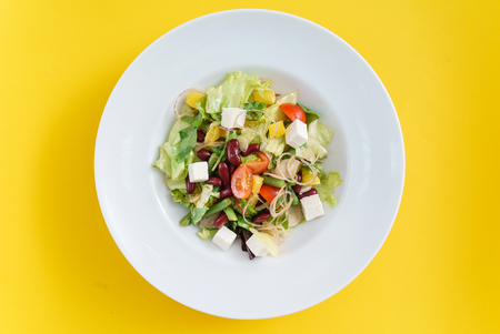 greek salad on yellow background