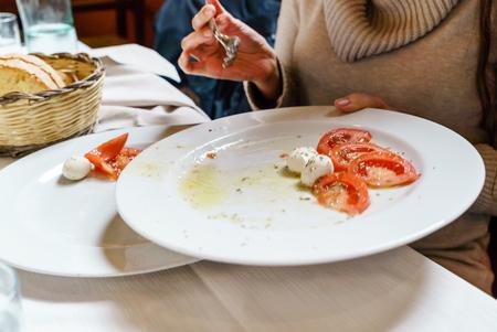 woman eating caprese salad in italian restaurant Stock Photo
