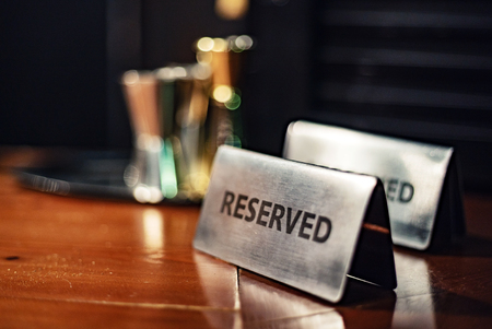 Reserved sign on a wooden table. Foto de archivo - 106227246
