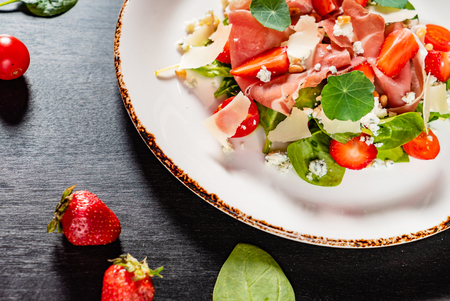salad with cherry tomatoes, cheese, strawberries and nasturtium leaves