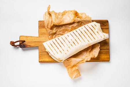 Chicken fajita wrap sandwich close up on wooden board Stock Photo