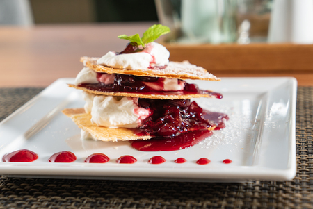 french pastry mille feuille with cream and berry sauce