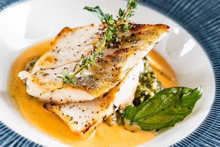 Filete de pescado frito. Bacalao con salsa y hierbas
