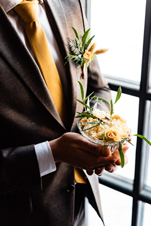 Stylish groom holds white wedding bouquet. Young groom in a suit.  Stock Photo