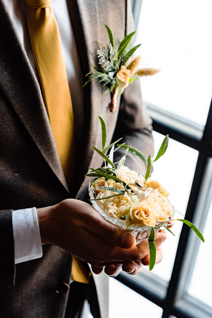 Stylish groom holds white wedding bouquet. Young groom in a suit.