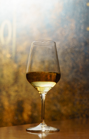 glass on white wine on the table in the bar, vertical image 版權商用圖片