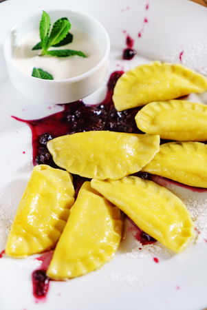 Dumplings, filled with cherries, berries. Pierogi, varenyky, vareniki, pyrohy - dumplings with filling, popular dish in many countries