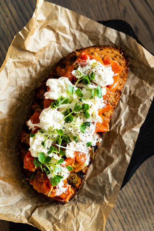 Italian bruschetta with roasted tomatoes, mozzarella cheese and herbs on a cutting board Stock Photo