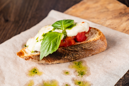 Traditional italian bruschetta with cherry tomatoes, cream cheese, basil leaves Stock Photo