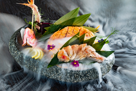 Japanese foods sashimi (raw sliced fish, shellfish or crustaceans) with smoke on the black 免版税图像