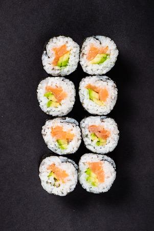 Sushi rolls set served on black stone slate on dark Stok Fotoğraf - 117174043