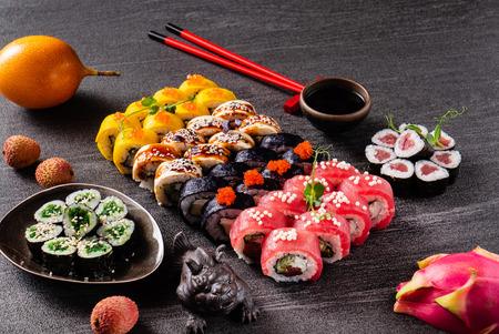 Sushi rolls set served on black stone slate on dark
