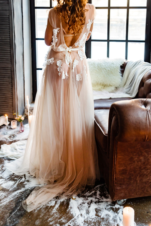 Wedding girl stand back in luxury wedding dress near window