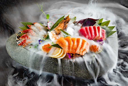 Japanese foods sashimi (raw sliced fish, shellfish or crustaceans) with smoke on the black