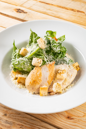 Fresh caesar salad in the white plate
