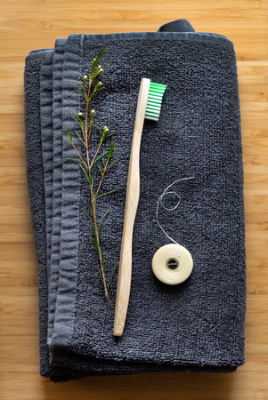 Eco natural bamboo toothbrushes and biodegradable silk  dental floss on the black towel,  sustainable lifestyle concept.